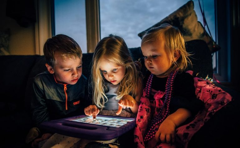three-children-looking-at-a-tablet-computer-3536480